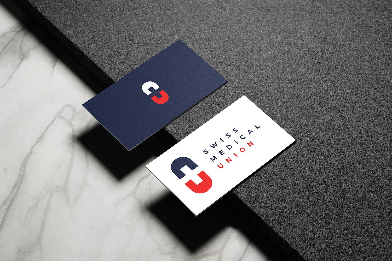 L'image représente 2 cartes de visite avec les einseignes de Swiss Medical Union posées sur une table en marbre