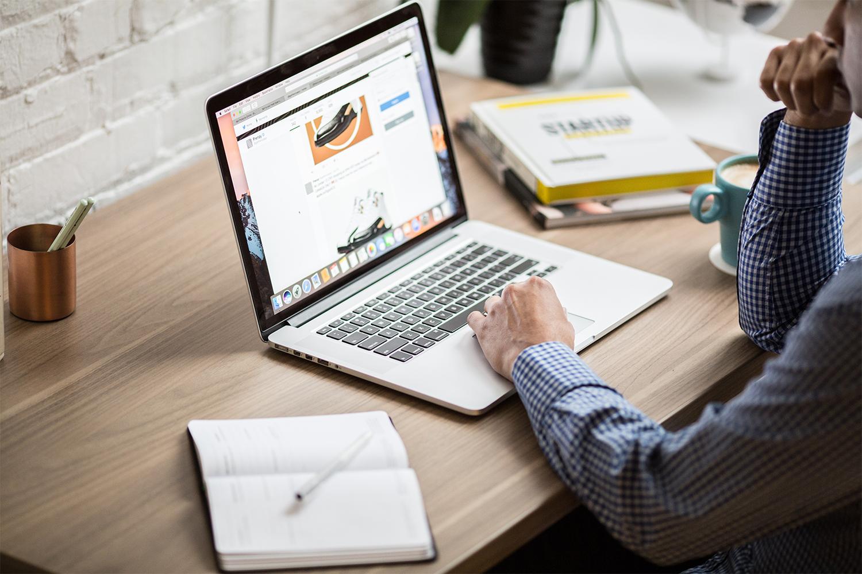 L'image représente un homme assis à son bureau, devant son ordinateur